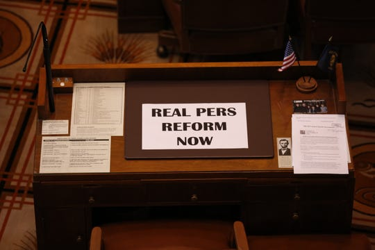 A sign reading 'Real PERS Reform Now' lies on the empty desk of a Republican senators after they didn't show up for Senate floor session at the Oregon State Capitol in Salem on May 7, 2019. Republicans denied the Senate a quorum so they could avoid voting on an education revenue bill.