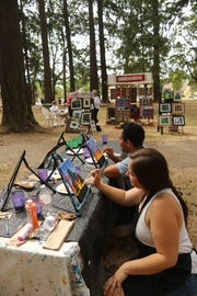 "Two artists paint at the Young at Art booth at the Englewood Forest Festival. Salem Cinema is hosting a screening of ""Sometimes a Great Notion"" on May 13 to benefit the festival."