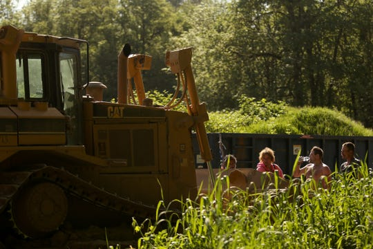 Several people stand in front of a bulldozer coming into a privately-owned rock quarry with a homeless camp near Wallace Marine Park in West Salem on May 7, 2019. Signs were posted throughout the camp recently stating personal property must be removed or it will be taken by the landowner and its designated agent starting May 7. An eviction can't be enforced until a court approves it.