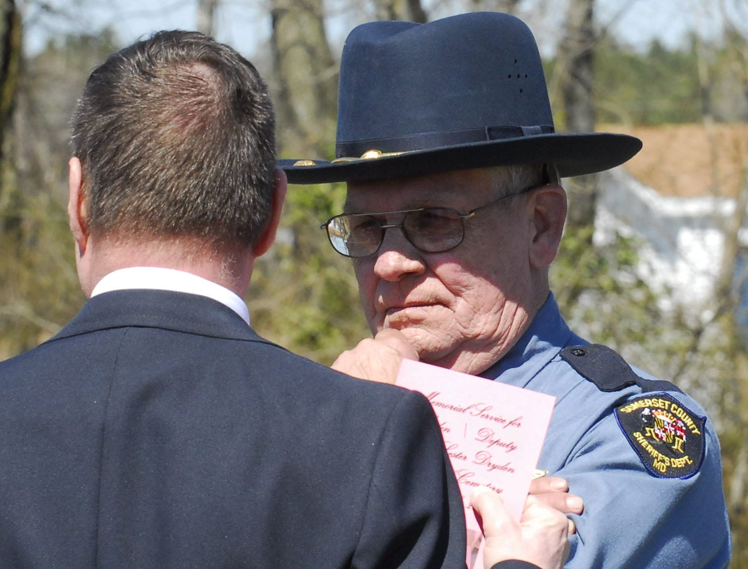 """Somerset County Sheriff Robert """"Bobby"""" Jones, right, speaks with Bill Dryden of Salisbury after the 2010 dedication of a new footstone at the grave of Lewis L. Dryden, a Somerset County deputy sheriff warden who was killed in the line of duty in 1924."""