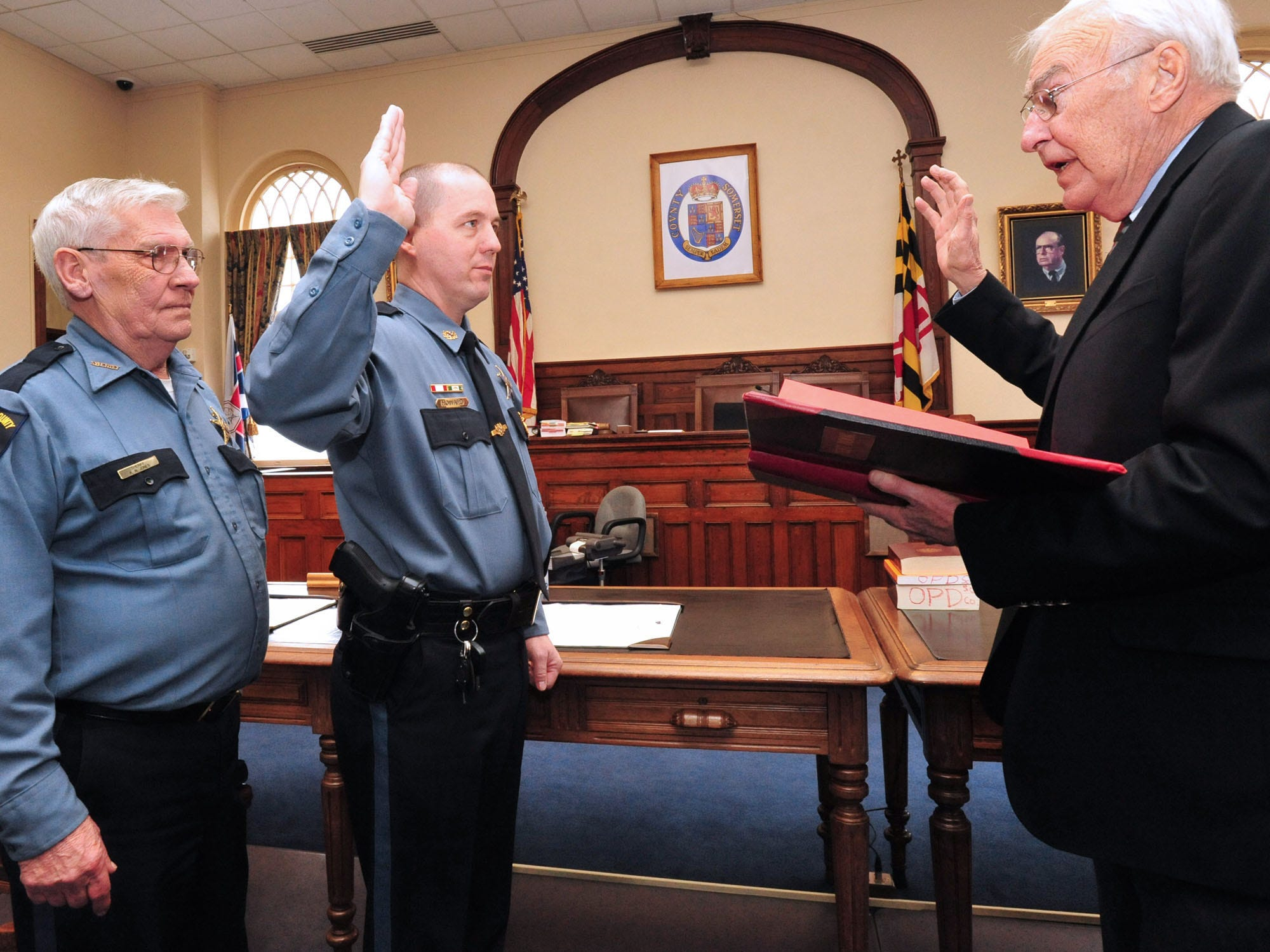 """Somerset County Sheriff Robert """"Bobby"""" Jones, left, looks on as Ronnie Howard, center, is sworn in as Chief Deputy of the Somerset County Sheriff's Office by Clerk of Court Ted Phoebus in 2010 at the courthouse in Princess Anne."""