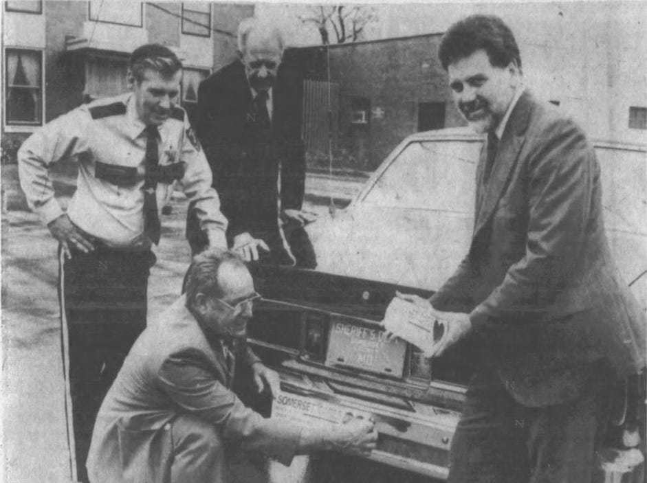 """Somerset County Sheriff Robert """"Bobby"""" Jones, left, Department of Energy Service Director John R. Somers and Peninsula Bank Vice President Phillip I. Gerald attach a """"Somerset Cares"""" bumper sticker to the sheriff's car in 1989."""