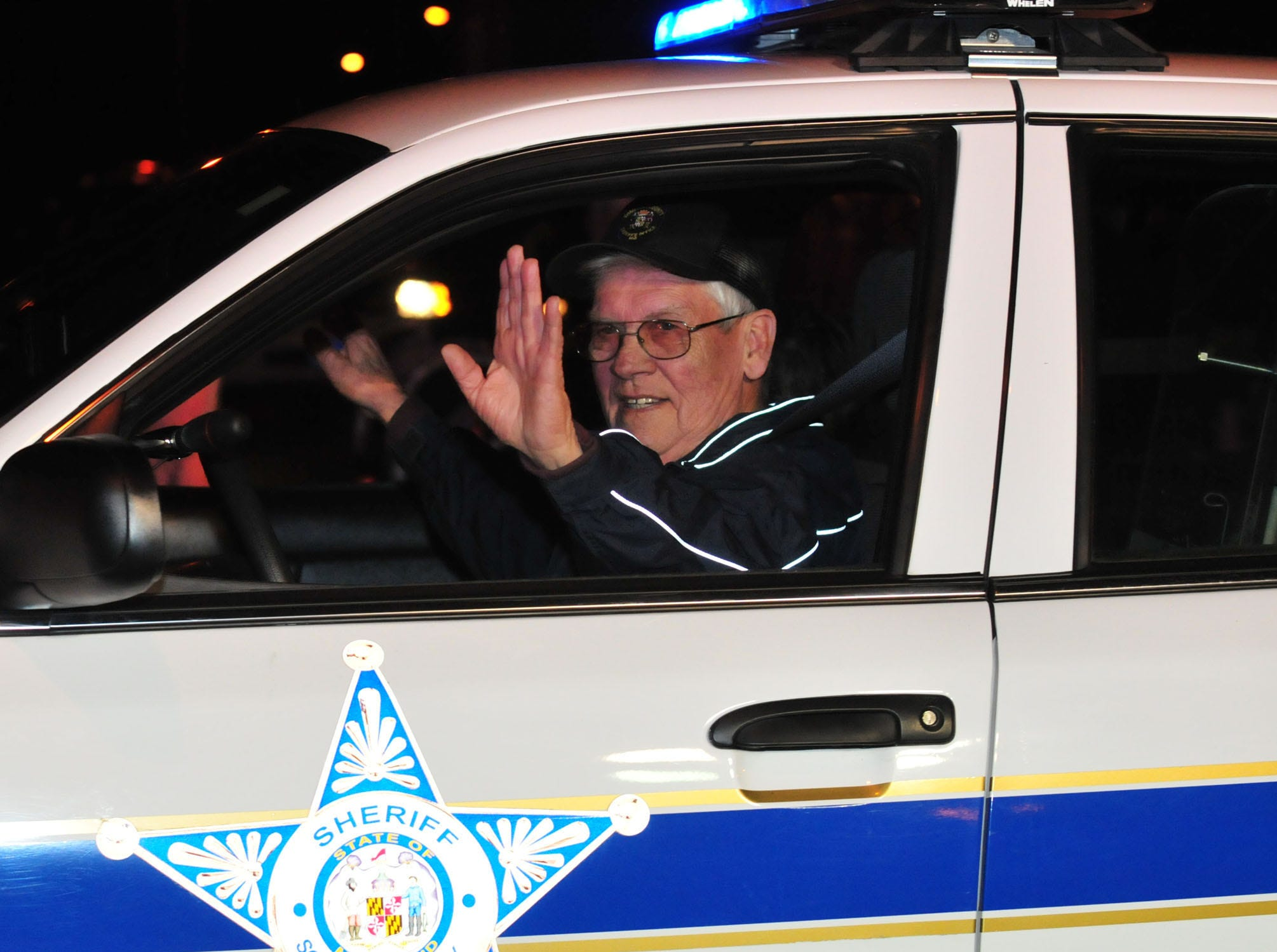 """Somerset County Sheriff Robert """"Bobby"""" Jones waves to the crowd at the Crisfield Christmas parade in December 2009."""