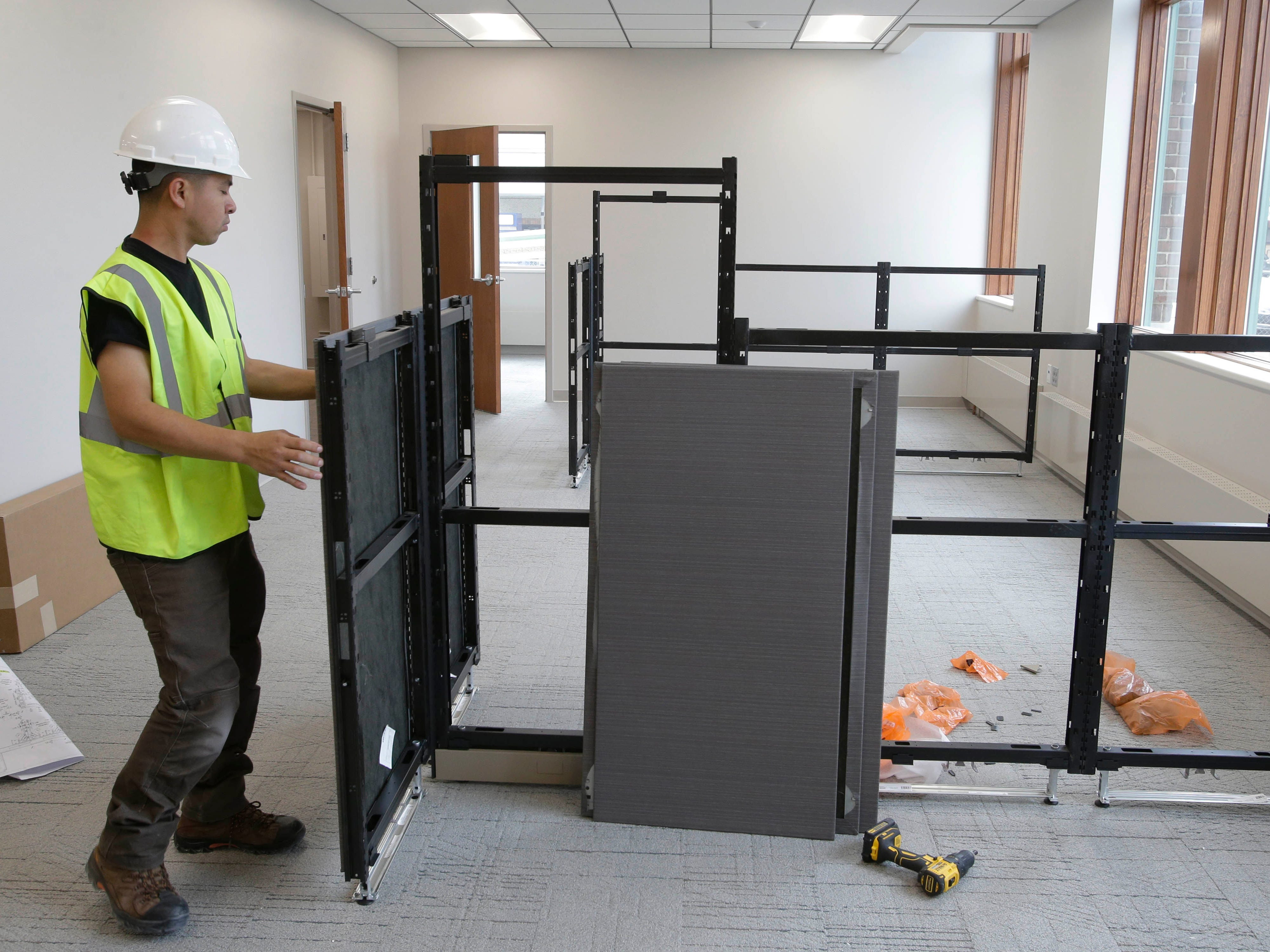 A contractor assembles a work station area as seen, Tuesday, May 7, 2019, in Sheboygan, Wis.