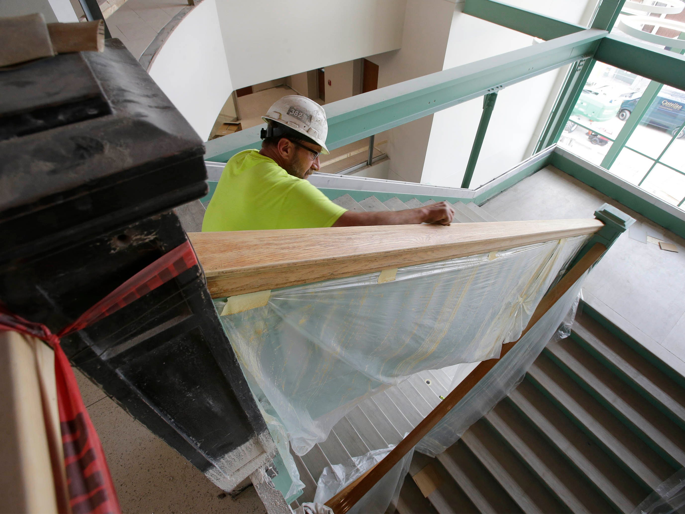 Jerry Ploeckelmann of Lee Color Studio of Manitowoc, Wis, prepares the hand rail at Sheboygan City Hall for refinishing, Tuesday, May 7, 2019, in Sheboygan, Wis.