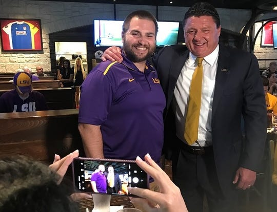 LSU football coach Ed Orgeron poses for a photo with David Moore taken by Moore's wife Lindsey. during Monday's LSU Coaches Caravan stop in Shreveport's Walk-Ons