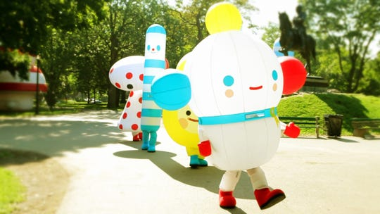 """""""The Rainbow King"""" leads a parade of """"Rainbow City"""" characters through Toronto."""
