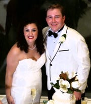 Kara Rae Bethard and Andrew Howard Alexander cut the cake at their wedding reception.