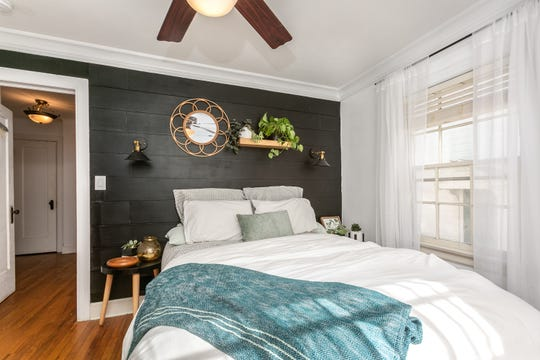 A paneled wall eliminates the need for a headboard. Large windows allow plenty of natural light to flood the room, balancing the dark tone of the wall.