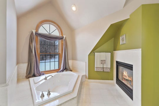 The en suite is complete with a soaking tub that sits just under a picture window and next to the fireplace.