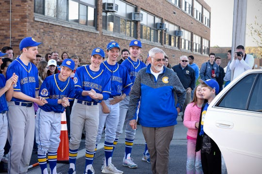 Members of Cathedral High School's baseball team surprise Bob Karn as he arrives at school in a limo Tuesday, May 7. Also pictured are Karn's grandchildren, Elizabeth and Cole Schwartz.