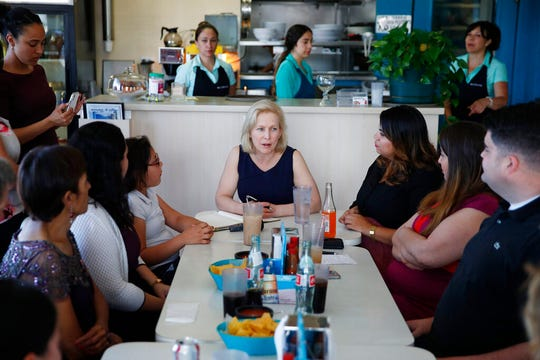 Democratic presidential candidate Sen. Kirsten Gillibrand, center, meets with community activists on immigration issues at a restaurant, Monday, May 6, 2019, in Las Vegas. (AP Photo/John Locher)