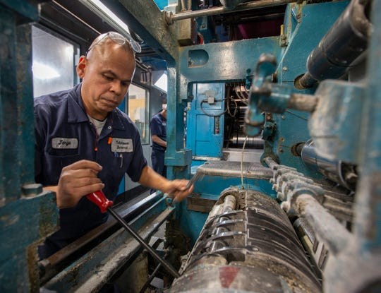 Press supervisor Jorge Arroyo-Avila makes mechanical adjustments to the old 1964  Goss Metro before one of the final press runs at the Tallahassee Democrat newspaper in Tallahassee, Fl.  The Goss Metro built in 1964 was purchased and shipped overseas to be installed in Tallahassee in 1979.