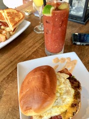 The Sunrise burger with a ground beef and brat patty, avocado, cheddar, Maple pepper bacon, a fried egg and Chipotle ranch dressing with a Bloody Mary and Mimosa in the background at Proper.