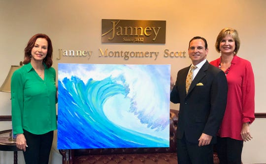 Michael Dadko with Sailfish Wealth Management Group of Janney Montgomery Scott in Stuart recently bought a painting at a Catch the Wave of Hope auction and fundraiser at the Kravis Center in West Palm Beach. The event was to help the organization raise money to abolish human trafficking through awareness, healing and action. Catch the Wave of Hope plans to open a home for trafficked girls. Pictured are Catch the Wave Founder Lynne Barletta, left, Michael Dadko and Catch the Wave President Janice Norman.