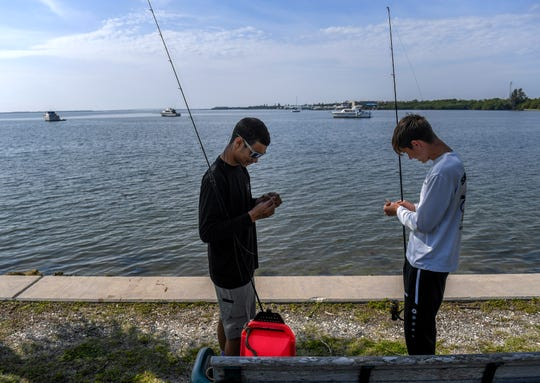 """Anglers Mike Enriquez 18 (left) and Lugh Huff, 17, both of Jensen Beach, prepare to cast their lines in the Indian River lagoon off the southwest corner of the Jensen Beach Causeway Park, where several boats are anchored near the shoreline. """"There's good people here, good environment, just to come here and chill, even if you are not fishing, a good place to come and hang out for the day,"""" Enriquez said. """"It's got a great view, even with the boats, it kind of puts some character into it."""" Martin County is planning to develop the area in the southwest corner of the lagoon at the causeway into a boat mooring field, with supporting infrastructure, and docks, with more than 50 mooring units available for rent by this winter season."""