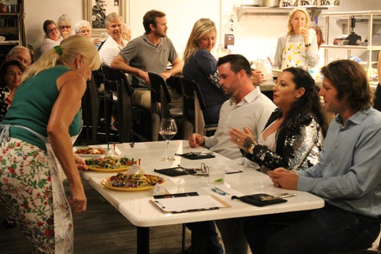 Chef Michelle Maguire presents her meal to Top Chef Martin County judges The Gafford's Taylor Wilson, seated, left, O Gourmet Bistro & Catering's Olivia Ostrow, and Chef's Table's Adam Fatigate.