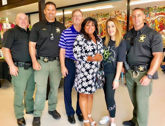 Members of the Martin County Sheriff's Office with Andrew and Robin Hunt, center, and Rina Shpiruk, second from right, at Hope Central in Stuart before heading out todeliver theEaster meal baskets to those in need.