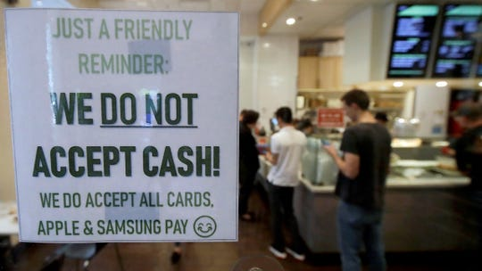 This Thursday photo shows a sign posted on a door alerting customers that cash is not accepted at Freshroll Vietnamese Rolls and Bowls in San Francisco. San Francisco is about to require brick-and-mortar retailers to take cash in payment for goods, joining Philadelphia and New Jersey in banning a practice that critics say discriminates against the poor.