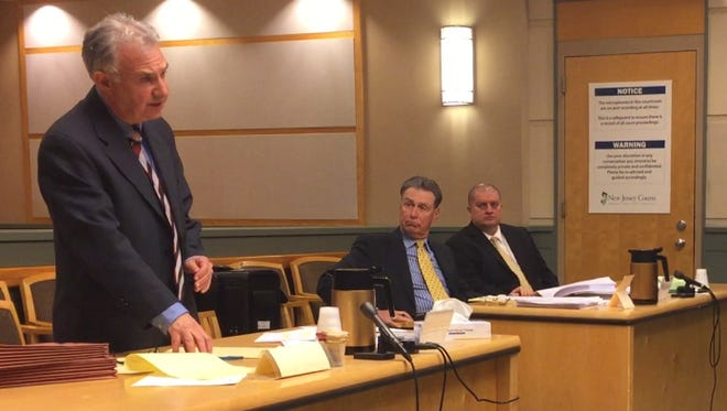 Cumberland County First Assistant Prosecutor Harold Shapiro (standing) argues the validity of an indictment against Millville police Officer Jeffrey E. Profitt (sitting, right) at a May 3 hearing in Superior Court. Profitt sits with defense counsel Michael Testa Sr.