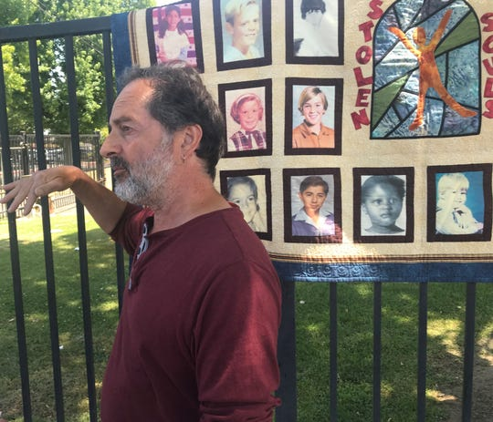 SNAP volunteer Joey Pisciteelli, a survivor of sexual abuse, calls for the Diocese of Fresno to release the names of clergy accused of sex abuse. Behind him is a quilt made of photos of survivors of clergy sex abuse.