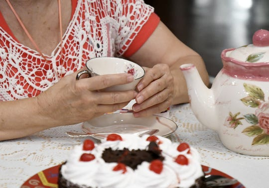 Crystal Burchnell holds her tea cup at a Death Cafe meeting at the Center for Spiritual Living on Friday, May 3, 2019.