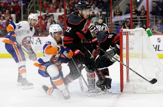 Carolina Hurricanes' Brett Pesce (22) and New York Islanders' Brock Nelson collide during the second period of Game 3 of an NHL hockey second-round playoff series in Raleigh, N.C., Wednesday, May 1, 2019.