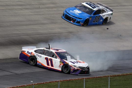 NASCAR Cup Series driver Denny Hamlin (11) spins as driver Alex Bowman (88) races by during the Gander RV 400 at Dover International Speedway.