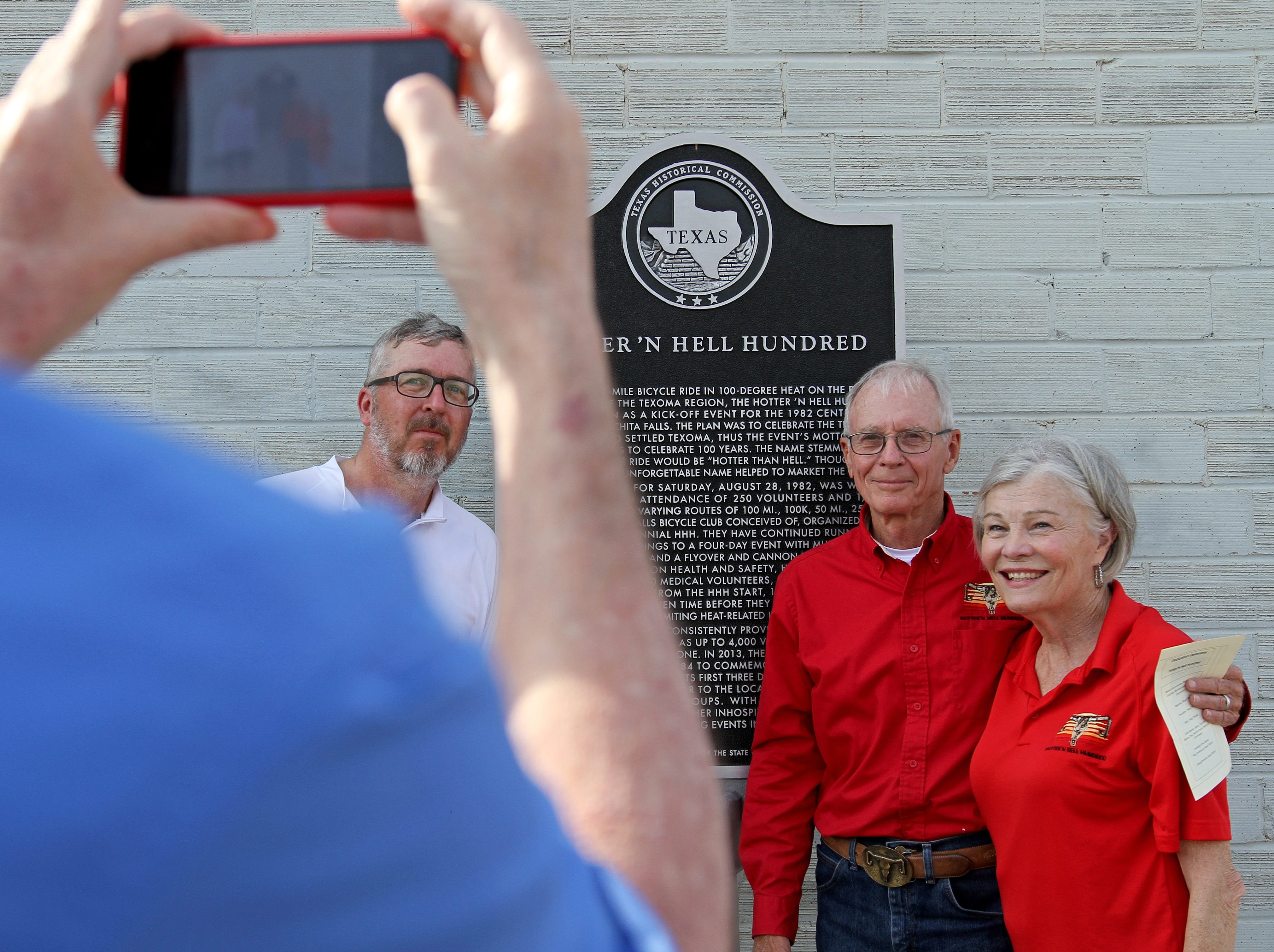 Joe Castelli, left, Roby and Renee Christie have their photo taken in front of the unveiled Hotter'N Hell Hundred Historical Marker Monday, May 6, 2019, at a dedication ceremony at the Hotter'N Hell Clubhouse at 104 Scott. The three were part of the original committee that started the HH100.