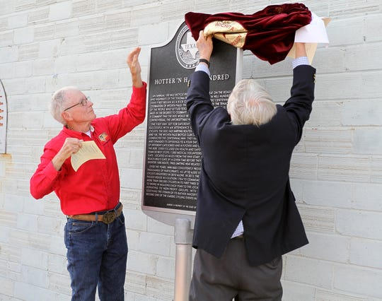 Roby Christie, left, and Robert Palmer, Wichita County Historical Commission, unveil the Hotter'N Hell Hundred Historical Marker Monday, May 6, 2019, at a dedication ceremony at the Hotter'N Hell Clubhouse at 104 Scott.