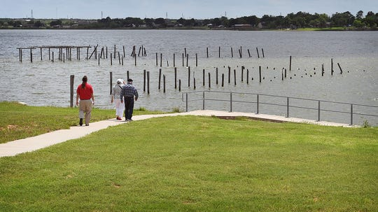 People attending the unveiling of a state historical marker at Lake Wichita Tuesday walk down for a closer look where the former Lake Wichita Pavilion and scenic pier were located.