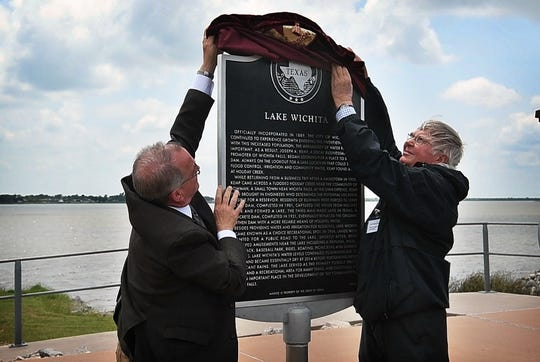 Steve Garner, left, and Robert Palmer unveil a Texas Historical Commission marker commemorating Lake Wichita and its place in Wichita Falls history.