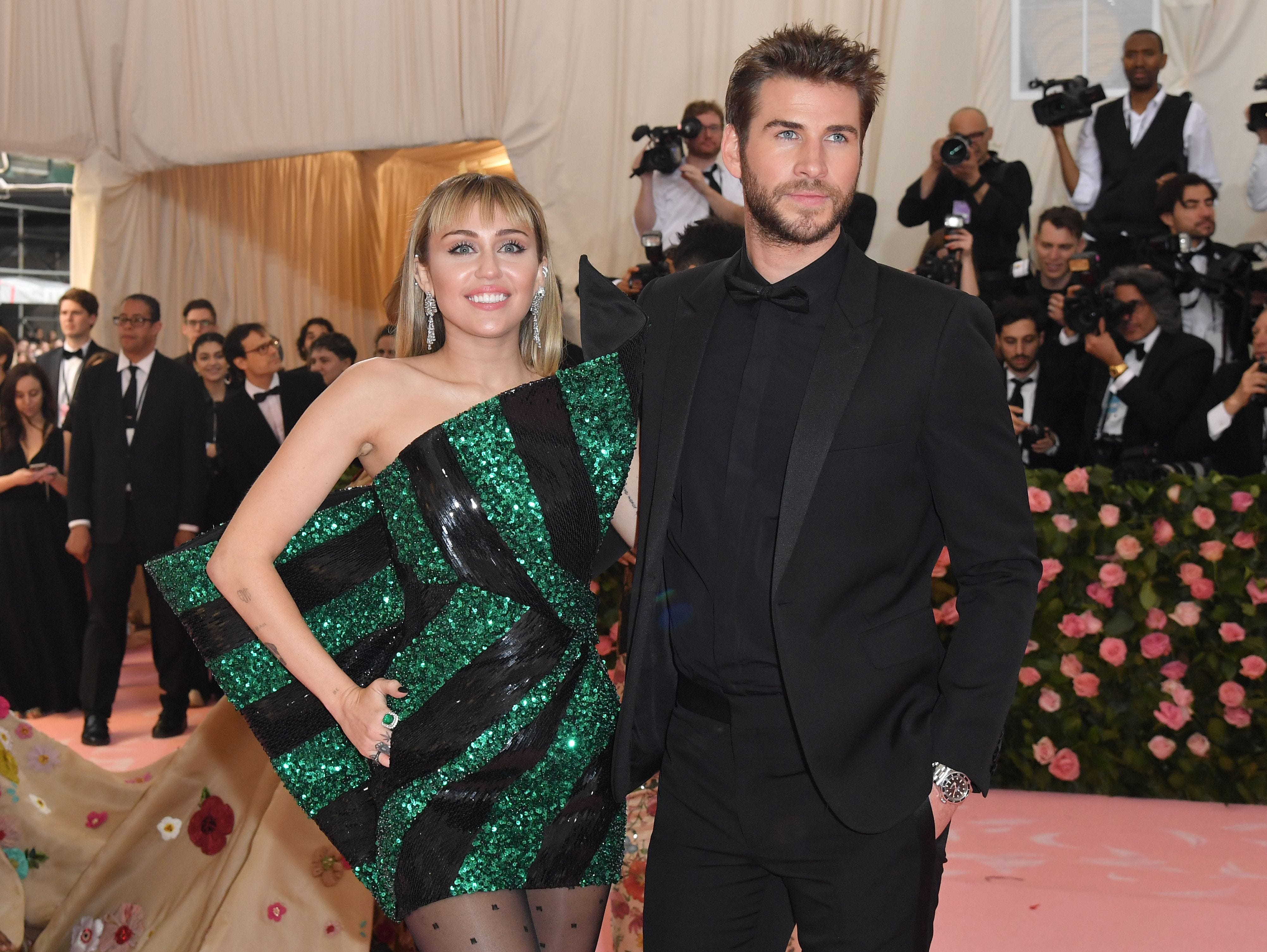 """TOPSHOT - Miley Cyrus (R) and Liam Hemsworth arrive for the 2019 Met Gala at the Metropolitan Museum of Art on May 6, 2019, in New York. - The Gala raises money for the Metropolitan Museum of Arts Costume Institute. The Gala's 2019 theme is Camp: Notes on Fashion"""" inspired by Susan Sontag's 1964 essay """"Notes on Camp"""". (Photo by ANGELA WEISS / AFP)ANGELA WEISS/AFP/Getty Images ORG XMIT: Annual Me ORIG FILE ID: AFP_1G83AL"""