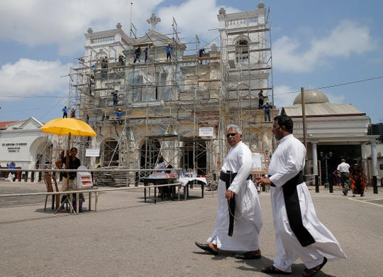 Sri Lankan Catholic priests walk outside the St. Anthony's church after it was partially opened for the first time since Easter Sunday attacks, in Colombo, Sri Lanka, Tuesday, May 7, 2019. Two bomb experts were among the suicide attackers who struck churches and hotels on Easter in Sri Lanka and all those directly involved in the bombings are either dead or under arrest, police said. (AP Photo/Eranga Jayawardena)
