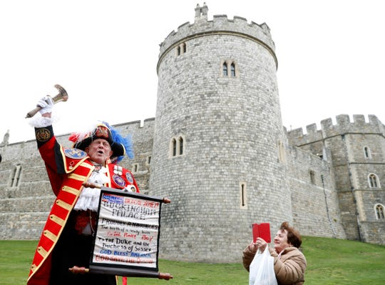 An unofficial Town Crier announces the birth of a baby boy born to Britain's Prince Harry and Meghan, the Duchess of Sussex, outside Windsor Castle in Windsor, England, on May 6, 2019.