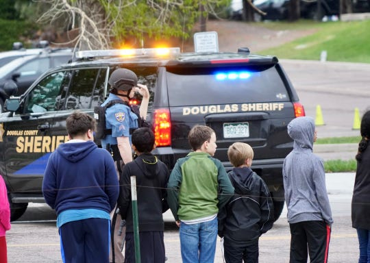 Police and school administrators load students onto school buses following a shooting in Highlands Ranch, Colorado.
