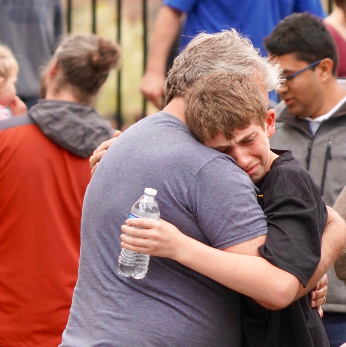 Robert Helfer, 13, hugs his grandfather, Shawn Helfer, 57, following a school shooting near Denver on Tuesday.