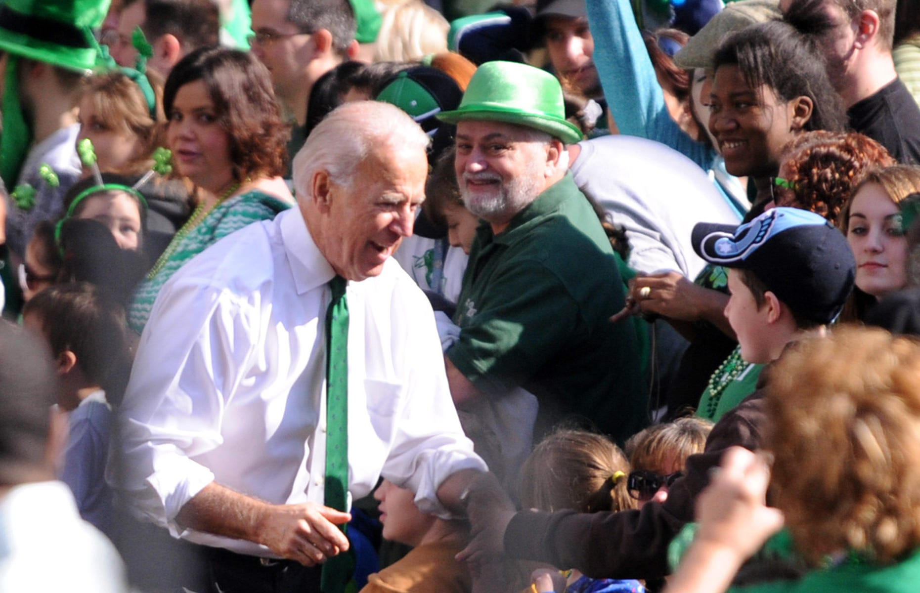 Then-Vice President Joe Biden greets people as he walks in the annual St. Patrick's Day Parade in Pittsburgh, Pennsylvania, March 17, 2012.