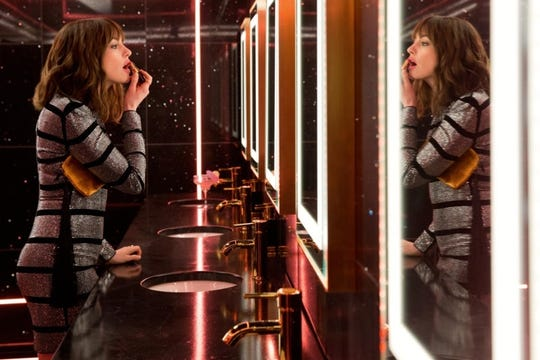 "Anne Hathaway gets ready for work in ""The Hustle."""