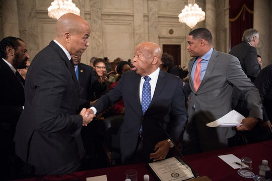 Sen. Cory Booker, D-N.J., shaking the hand of Rep. John Lewis, D-Georgia, along with Rep. Cedric Richmond, D-Louisiana and the former chair of the Congressional Black Caucus, right,  before a Senate Judiciary Committee in 2017.