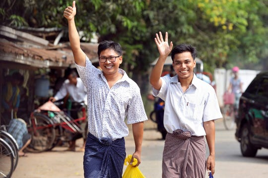 Reuters journalists Wa Lone, left, and Kyaw Soe Oo gesture as they walk to Insein prison gate after being freed in a presidential amnesty in Yangon on May 7, 2019.