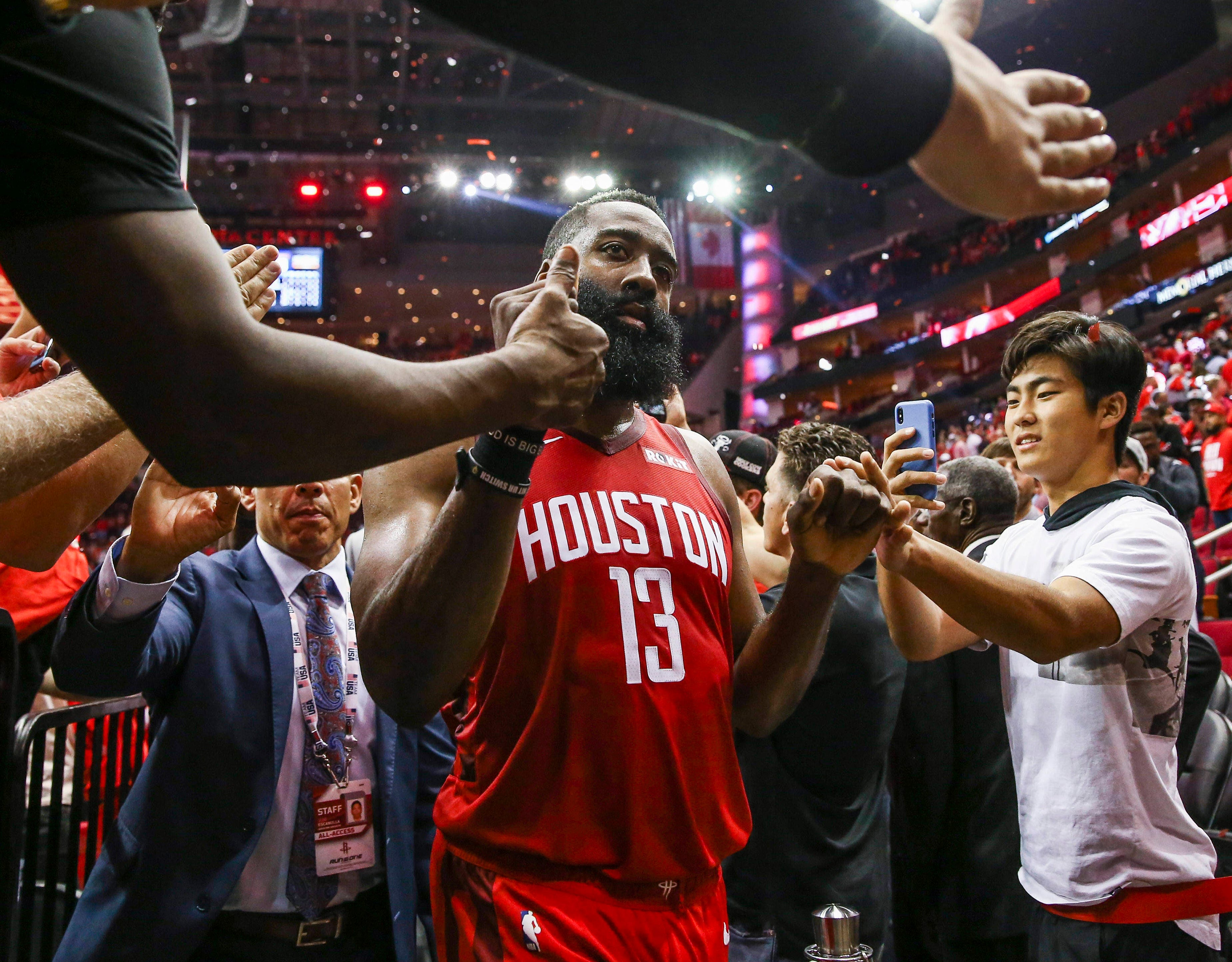 May 6: Rockets guard James Harden gets high-fives from the fans as he leaves the floor after beating the Warriors in Game 4.