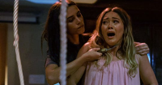 "Sharon Tate (Hilary Duff, right) is terrorized by Manson Family member Sadie (Bella Popa) in the horror film ""The Haunting of Sharon Tate."""