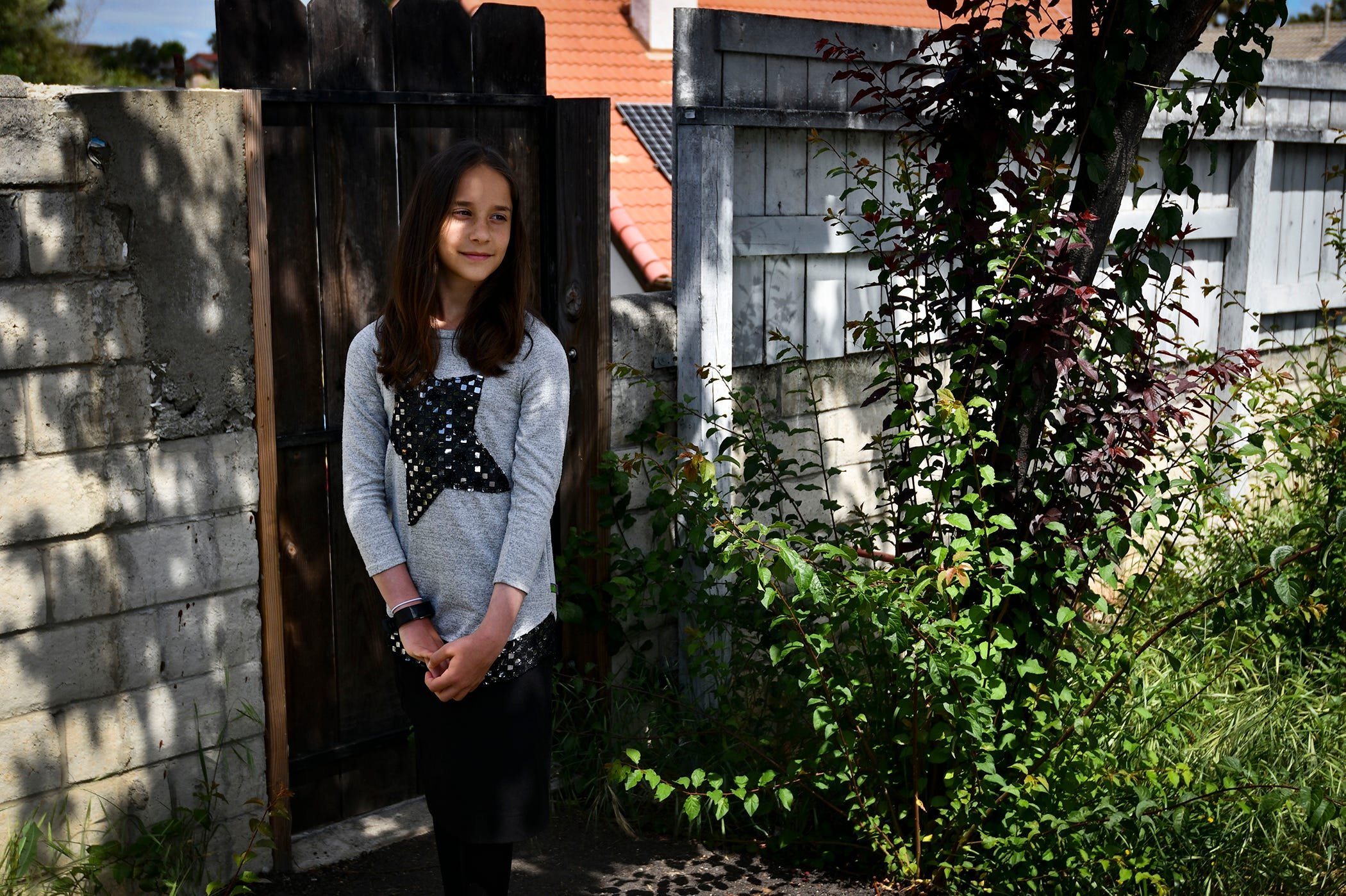 Netanya Trestman, 11, was just outside of the sanctuary babysitting children when the shooting started. After hearing gunshots, she immediately ran down the stairs behind the church and ran to find hiding. Netanya poses for an image in front of a gate behind the synagogue that she ran through to hide from the active shooter.