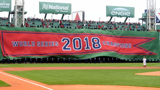 Boston's World Series titlebanner is unrolled over the Green Monster.