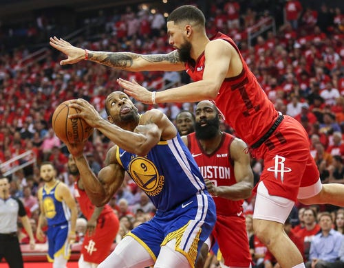 May 6: Warriors forward Andre Iguodala (9) looks for room to shoot over Rockets defender Austin Rivers (25) during Game 4.