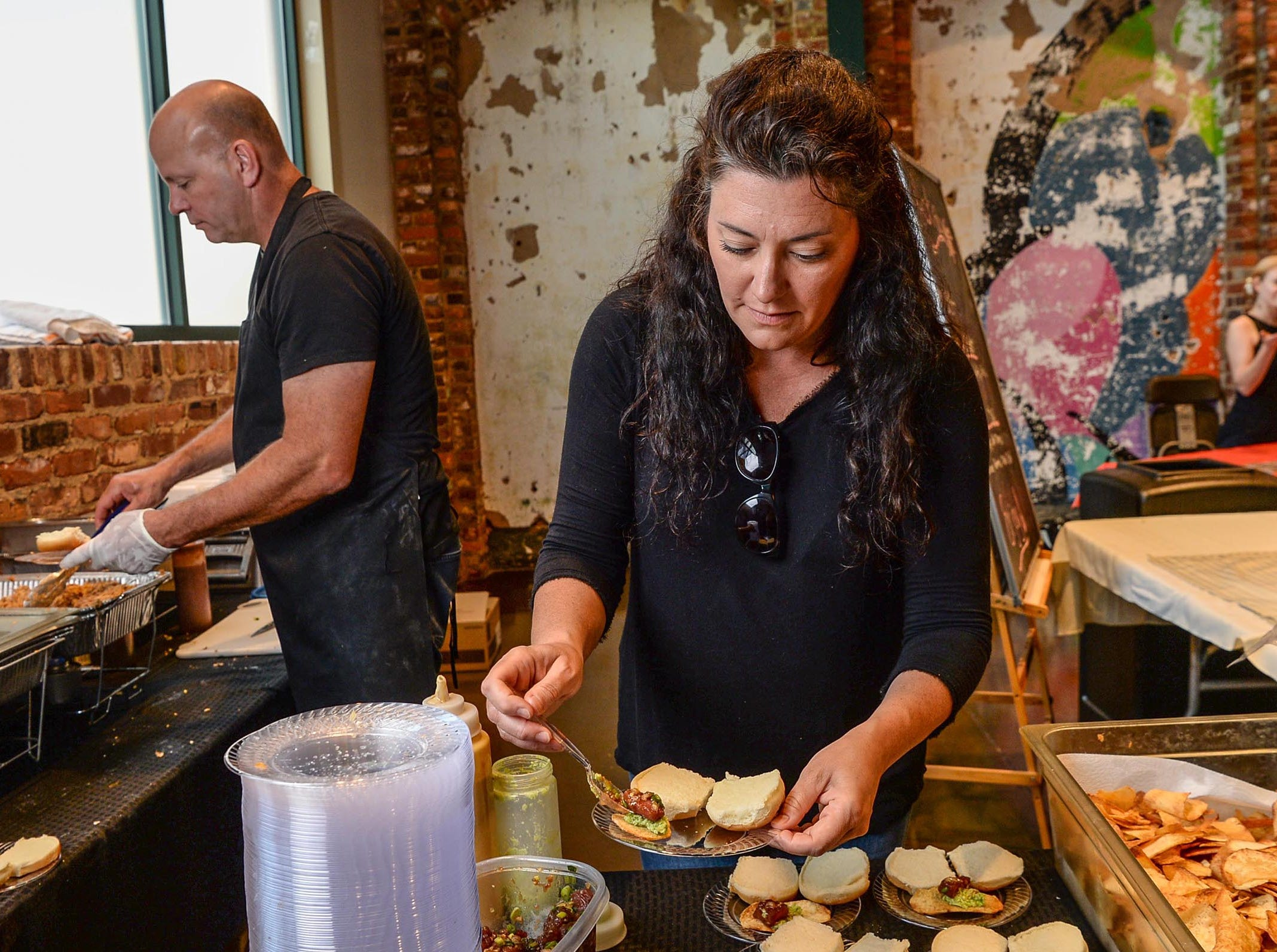 Jennifer Hawkins, right, and Erick Omick, left, of Sadler's Creek BBQ in Anderson create plates with The Kahlua Pig Slider with Kimchee pineapple salsa and Ahi Poke Chip with sauce during the Anderson Area YMCA Ralph Hayes Toyota Taste of Anderson at The Bleckley Station Tuesday. Proceeds from the Aloha theme party benefit programs and services of the Anderson Area YMCA.