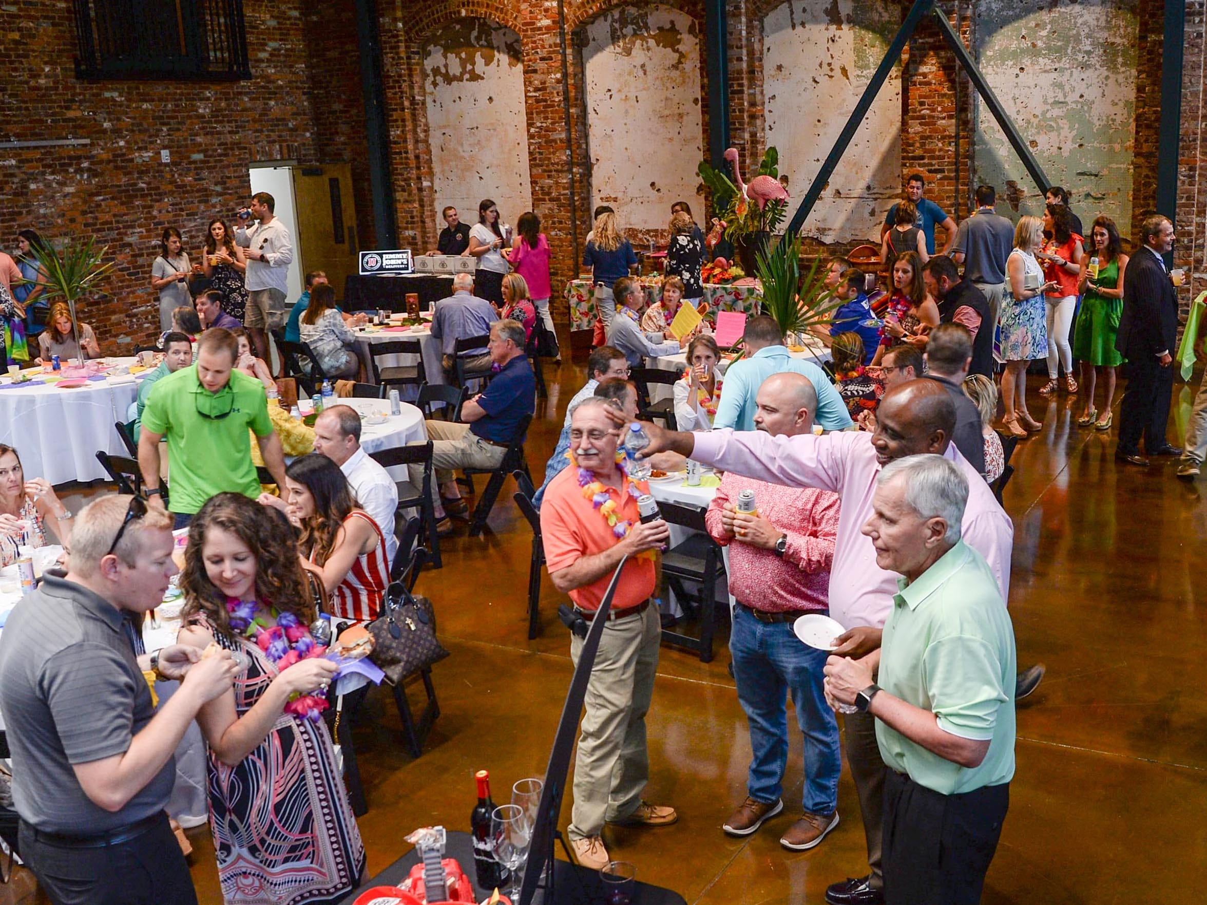 A large crowd mingles and eats food during the Anderson Area YMCA Ralph Hayes Toyota Taste of Anderson at The Bleckley Station Tuesday. Proceeds from the Aloha theme party benefit programs and services of the Anderson Area YMCA.