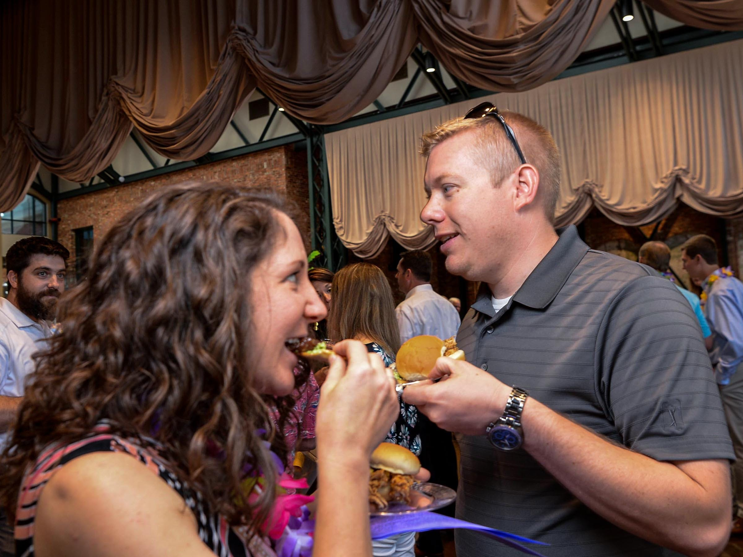 Sarah and Matt Anderson try the The Kahlua Pig Slider with Kimchee pineapple salsa and Ahi Poke Chip with sauce from Sadler's Creek Barbecue in Anderson, during the Anderson Area YMCA Ralph Hayes Toyota Taste of Anderson at The Bleckley Station Tuesday. Proceeds from the Aloha theme party benefit programs and services of the Anderson Area YMCA.