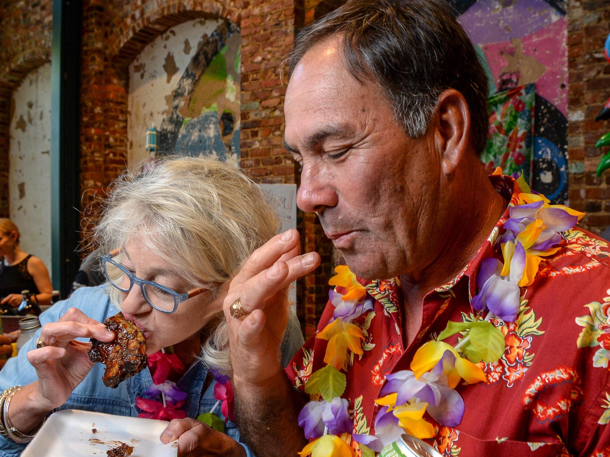 Angela and Randy Reeves of Anderson try the barbecue ribs from Texas Roadhouse at the Anderson Area YMCA Ralph Hayes Toyota Taste of Anderson at The Bleckley Station Tuesday. Proceeds from the Aloha theme party benefit programs and services of the Anderson Area YMCA.